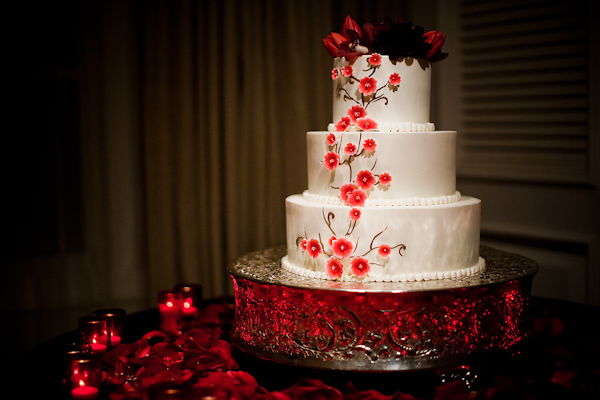 Beautiful White Three Tiered Round Wedding Cake With Coral And Red Floral Accents On A Vintage