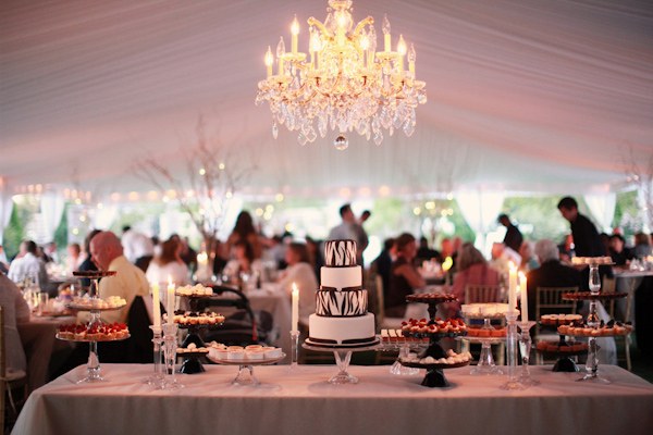 photo of the dessert table under a chandelier and tent of the outdoor reception - photo by Northwest wedding photographer Michele Waite