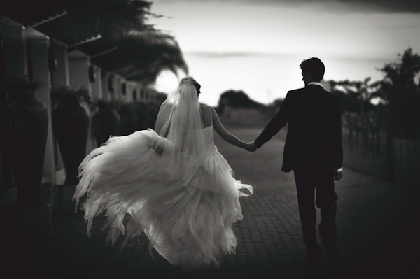 Beautiful black and white photo of the happy couple walking away holding hands wedding photo