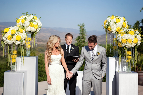 Beautiful sunny, outdoor wedding ceremony with white and yellow floral arrangements - Photo by April Smith & Co.