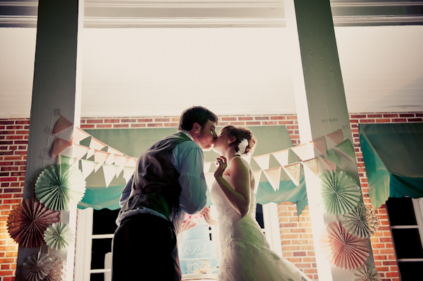 Bride and groom in front of pastel-colored wedding decor - Wedding Photo by Elizabeth Davis