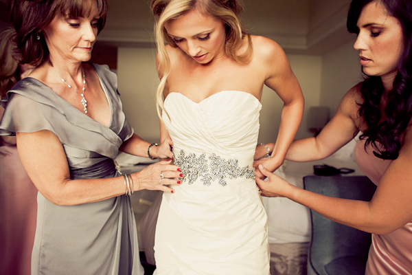 Bride getting dressed on her wedding day - wedding photo by Focus Photography