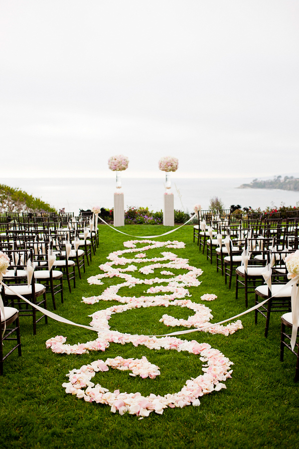 Outdoor aisle with light pink and white florals and petal decoration - wedding photo by Focus Photography