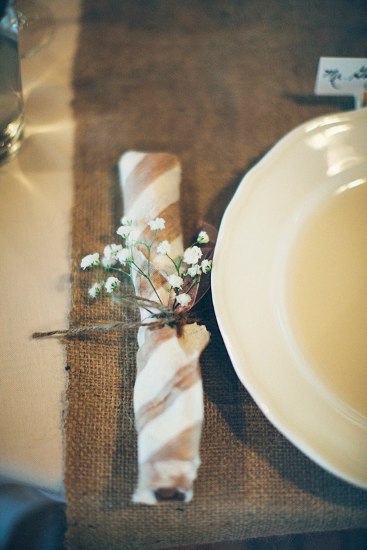 Place setting featuring brown and white striped napkin tied with white flower - Photo by The Schultzes