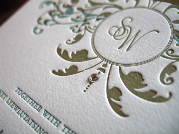 details of white classic style invitation with gold and aqua floral swirls and monogram with rhinestone - photo of wedding invitations designed by Brown Sugar Designs
