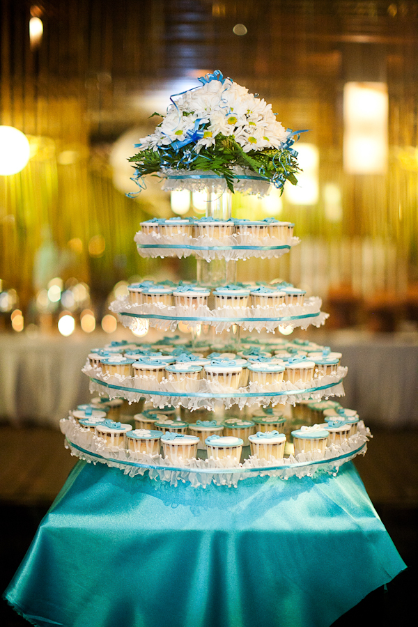 a tiered platform holds blue and white cupcakes with floral detail on top - traditional Indonesian wedding in Bali - photo by Portland wedding photographer Bunn Salarzon