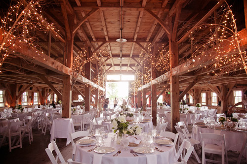 Rustic barn wedding with twinkling lights and elegant white decor - Photo by Emily Delamater