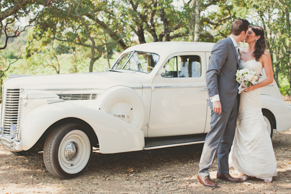 couple kisses in front of white vintage car - warm, sunny, Sonoma California vineyard wedding photo by California wedding photographers EP Love