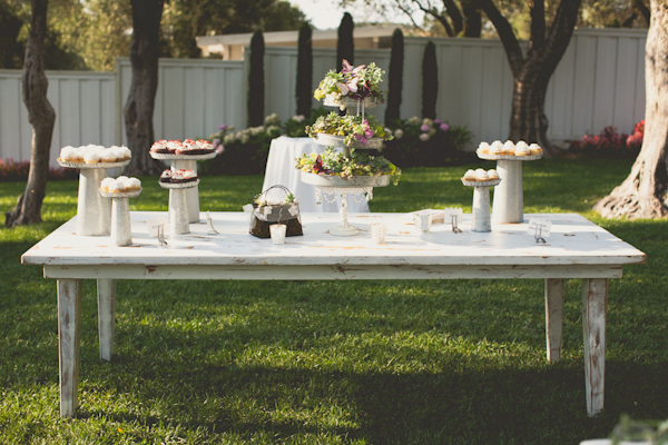 white wooden table setting with metal dessert stands and cupcakes - warm, sunny, Sonoma California vineyard wedding photo by California wedding photographers EP Love