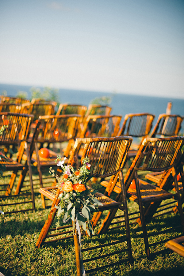 wooden chairs with orange floral arrangements at seaside ceremony site - Sayulita, Mexico destination wedding photo by Mexico wedding photographer Jillian Mitchell