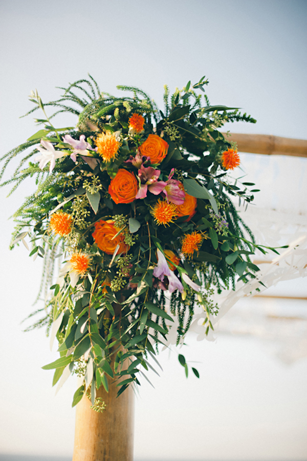 orange floral arrangement at ceremony site - Sayulita, Mexico destination wedding photo by Mexico wedding photographer Jillian Mitchell