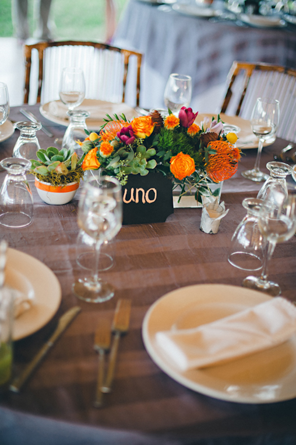 table setting with orange and dark pink flower centerpiece - Sayulita, Mexico destination wedding photo by Mexico wedding photographer Jillian Mitchell