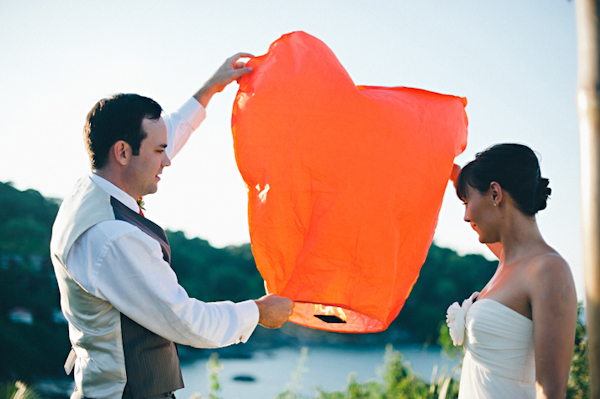 bride and groom release an orange lantern into the sky - Sayulita, Mexico destination wedding photo by Mexico wedding photographer Jillian Mitchell