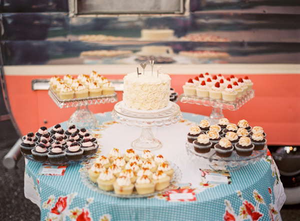 Cupcake and wedding cake table on blue and red tablecloth - Photo by Michelle Warren Photography