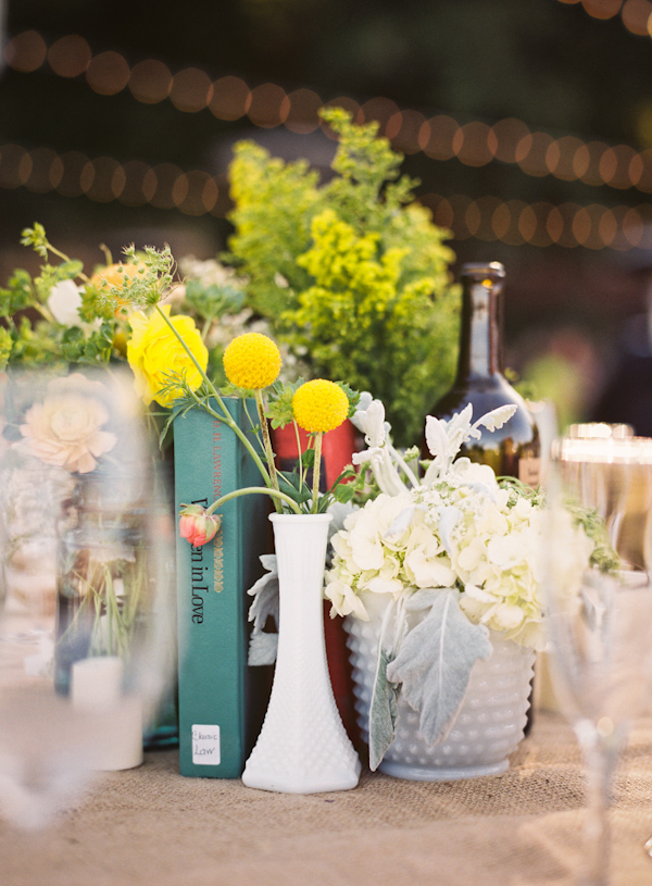 Eclectic tabletop featuring books and various floral decor - Photo by Michelle Warren Photography