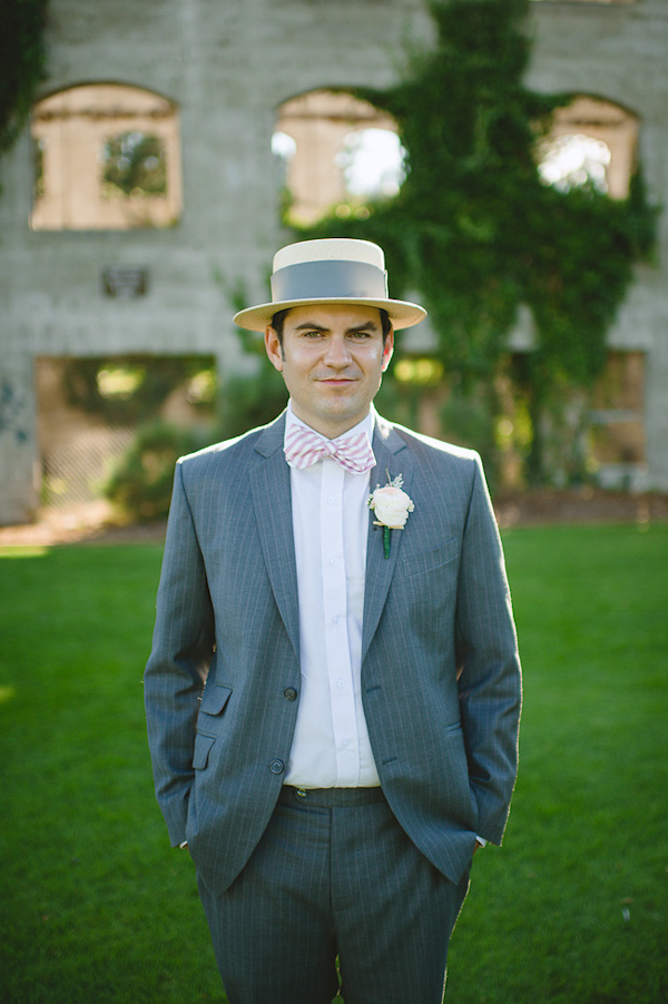 Handsome groom wearing gray suit, pink bowtie and top hat - Photo by Nordica Photography