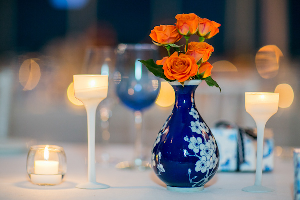 Vibrant orange roses in navy blue and white floral vase - Photo by Sarah Tew Photography