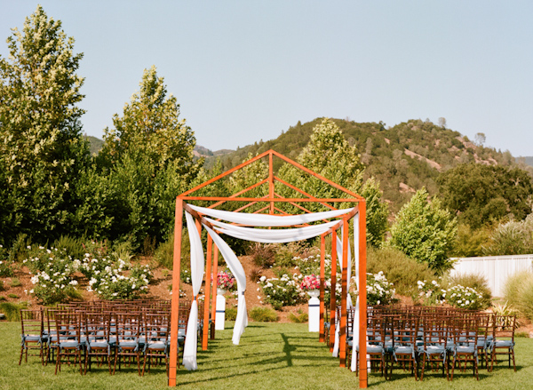 Outdoor wedding ceremony in beautiful Napa Valley with wooden aisle structure - Photo by Sylvie Gil Photography