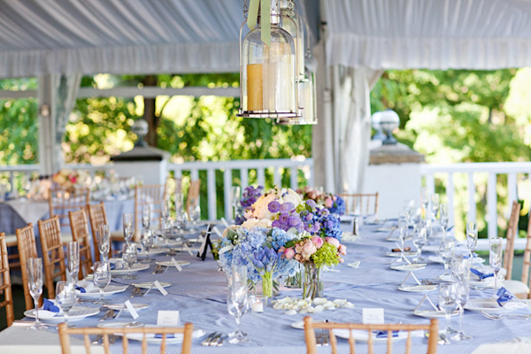 long light blue table setting with flower centerpieces and glass lanterns hanging above - preppy New York Sagamore resort wedding photo by New York wedding photographer Tracey Buyce