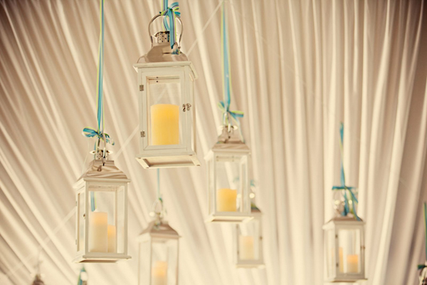 candles hang in class lanterns from tent ceiling - preppy New York Sagamore resort wedding photo by New York wedding photographer Tracey Buyce