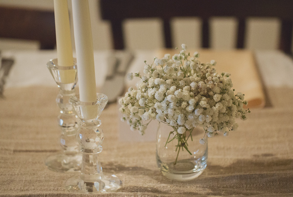 Small baby's breath reception table arrangement on burlap tablecloth - Photo by Whitewall Photography
