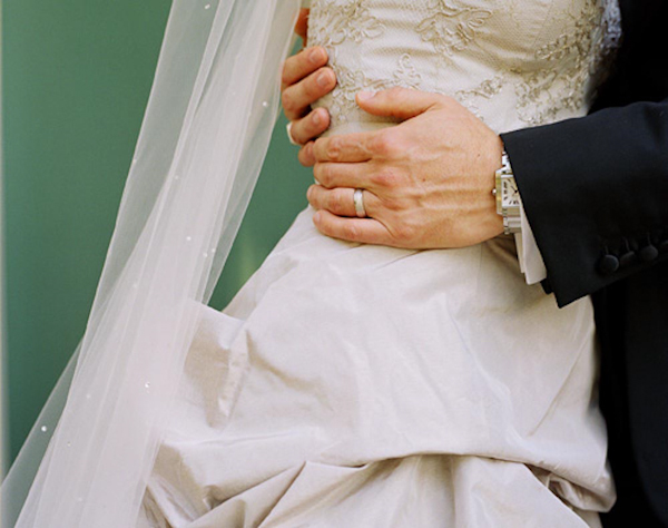 Close-up of bride and groom embrace - wedding photo by top Austin based wedding photographers Q Weddings