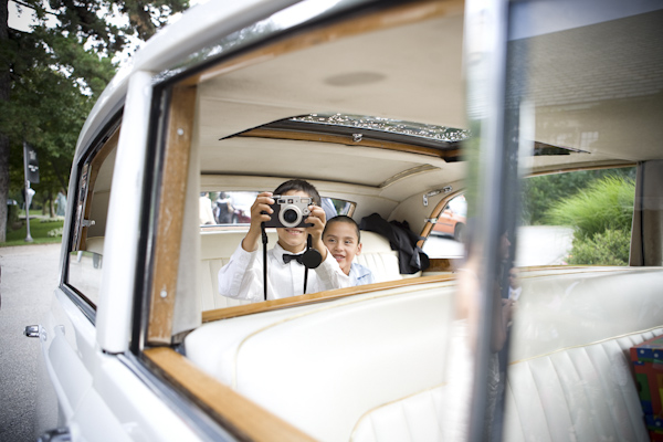 kids sitting in the car taking pictures of the bride and groom- wedding photo by top Canadian wedding photographer Rebecca Wood
