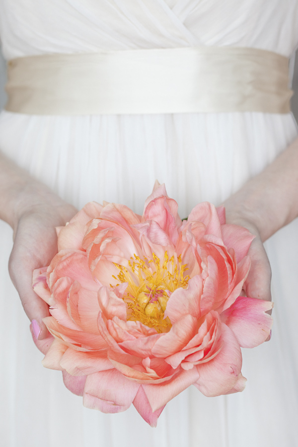 Bride holding a big pink flower- wedding photo by top Canadian wedding photographer Rebecca Wood