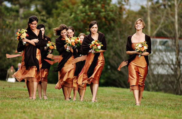 Bridesmaids In Orange Knee Length Dresses Covered By Dark Brown Shawls Photo North Carolina