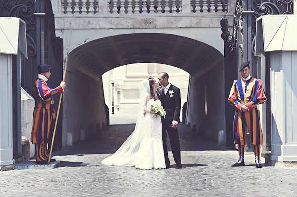 newlywed kissing in front of historic building in Rome - wedding photo by top Rome based destination wedding photographer Rochelle Cheever, Rome Weddings Photography
