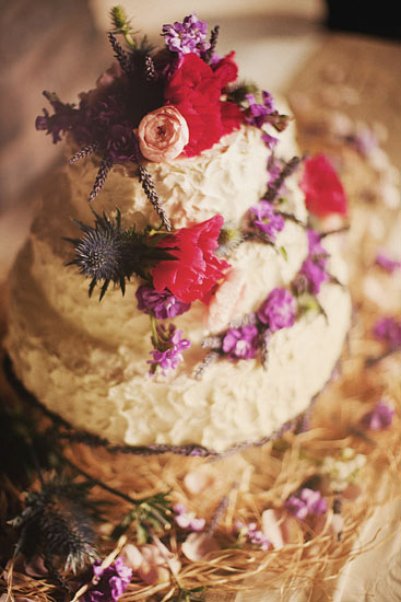 Rustic style weding cake with pops of bright pink and purple flowers - Photo by Ryan Flynn Photography