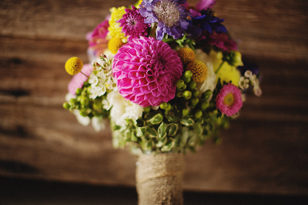 Colorful and rustic bridal bouquet featuring shades of bright pink, yellow and green - Photo by Ryan Flynn Photography