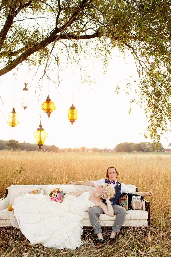 Couple lounging on outdoor sofa with vintage inspired lights hanging from the trees - Photos by Studio 6.23