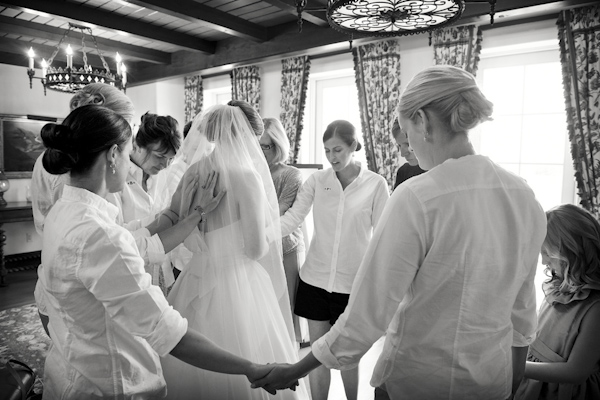 Beautiful photo of friends and family surrounding the bride in prayer - photo by top Atlanta-based wedding photographer Scott Hopkins Photography
