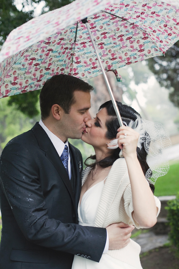 the happy couple kissing under umbrella in the rain - photo by Orange County wedding photographer Stephanie Williams