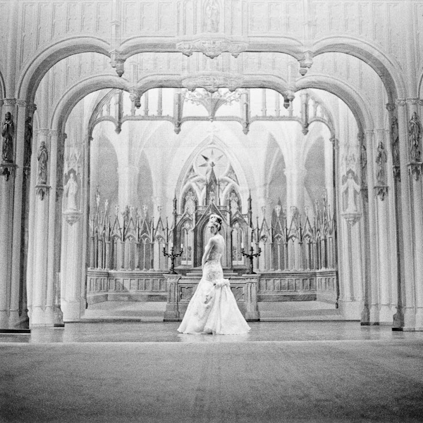 black and white photo of beautiful bride standing in a historic cathedral - photo by New Mexico based wedding photographers Twin Lens