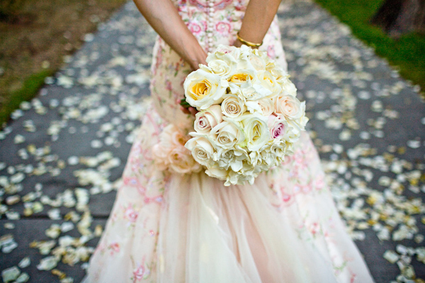 bride wearing a beautiful champagne ball gown style dress with dark pink and light green designs with a light pink rose bouquet - photo by New Mexico based wedding photographers Twin Lens