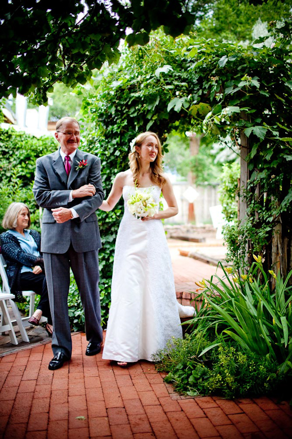 beautiful bride and father walking down the aisle during the ceremony - bride is wearing a white a-line dress with a white and yellow bouquet - photo by New Mexico based wedding photographers Twin Lens
