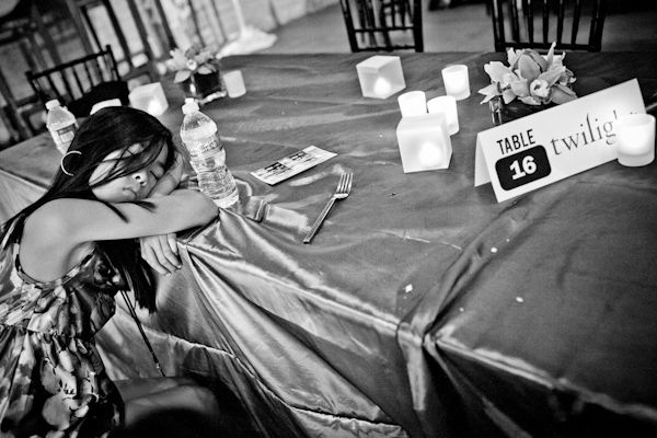 black and white photo of adorable girl napping on table during reception - photo by New Mexico based wedding photographers Twin Lens Images