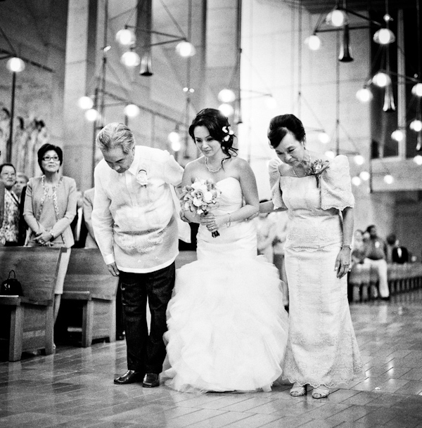 black and white photo of bride escorted down the aisle by parents - photo by New Mexico based wedding photographers Twin Lens Images