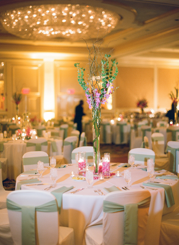 Light Green And Dark Pink Table Setting In A Ballroom Reception