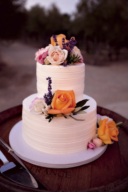 white wedding cake with pink and orange flowers for vineyard wedding at Sunstone Winery, photo by Ashleigh Taylor Photography