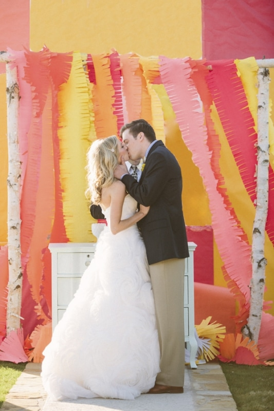 colorful pink, orange yellow streamer backdrop at wedding ceremony, photo by Taylor Lord Photography
