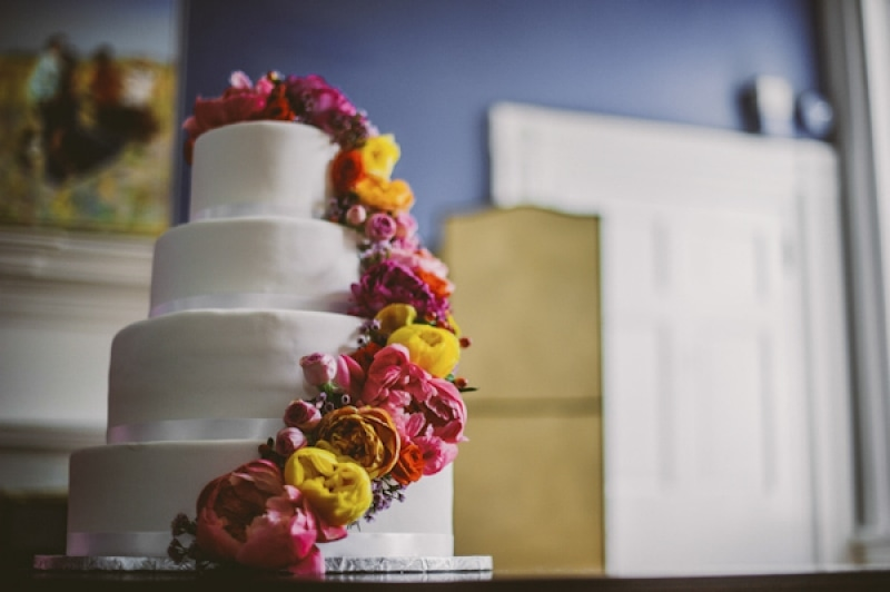 bright flowers on clean white tiered cake, photo by The Oberports
