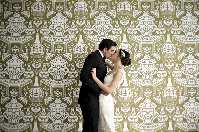 1920s inspired bride and groom kissing in front of decorative wallpaper, photo by Kristen Weaver Photography
