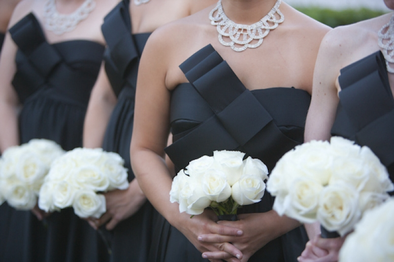 bridesmaids with long black dresses with large bow and white rose bouquets, photo by JSPStudio