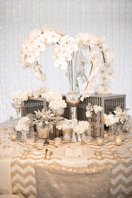 white orchid centerpiece on gold chevron print table, photo by Kristen Weaver Photography