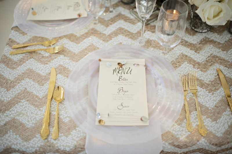 place setting with gold chevron print and gold flatware, photo by Kristen Weaver Photography