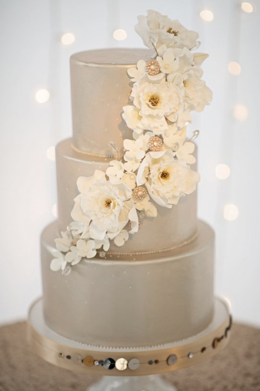 silver tiered wedding cake with white florals on metallic cake stand photo by kristen weaver