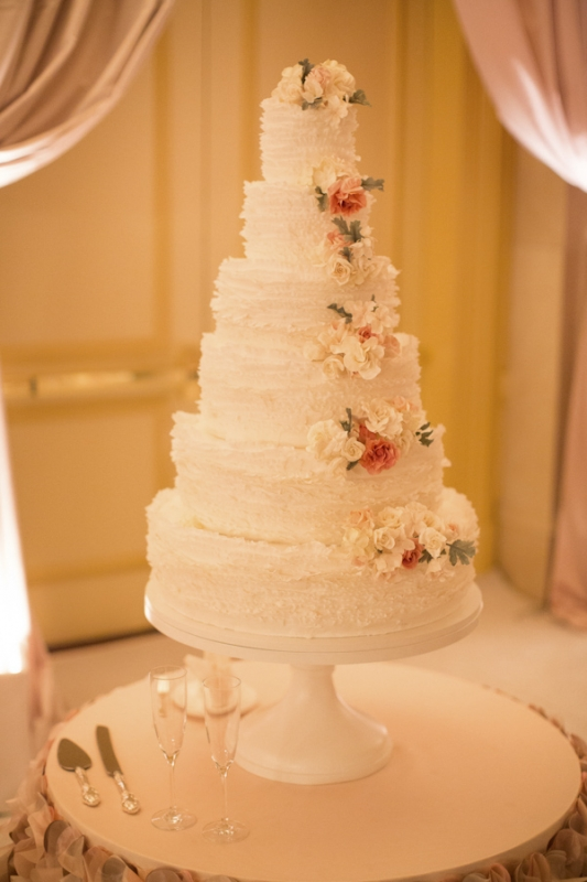 ruffled white tiered wedding cake with pink florals, photo by Ira Lippke Studios
